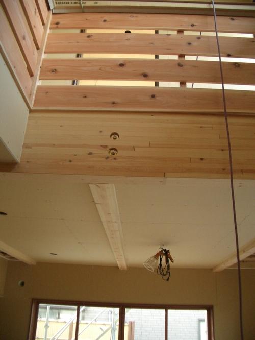 吹き抜けの手すり。一階天井は高くして梁を出した。